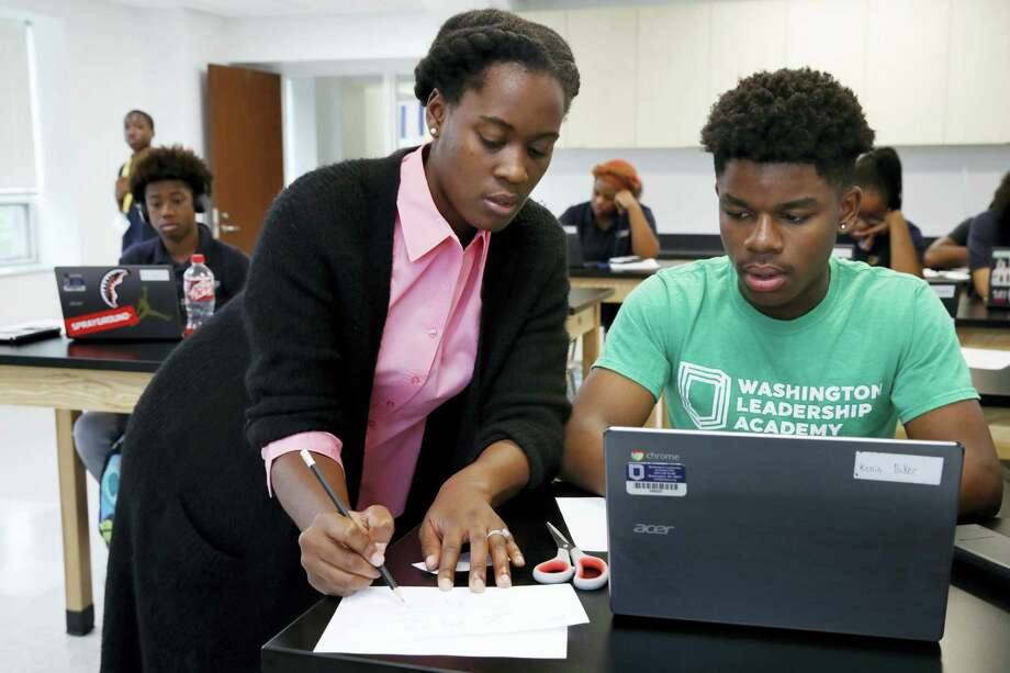 "Britney Wray, a math teacher at Washington Leadership Academy, helps sophomore Kevin Baker, 15, with a math problem during class in Washington, Wednesday, Aug. 23, 2017. Students took diagnostic tests using special software. As they solved math problems on their laptops, the system diagnosed their proficiency levels in real time, part of ""personalized learning."" This approach uses software, data and constant monitoring of student progress to adapt teaching to each child's strengths, weaknesses, interests and goals and enable them to master topics at their own speed. Photo: AP Photo — Jacquelyn Martin  / Jacquelyn Martin"