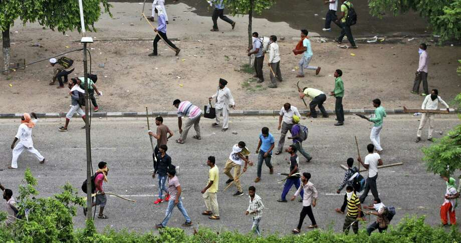 Dera Sacha Sauda sect members hold sticks and stones as they go on a rampage near a court in Panchkula, India, Friday, Aug. 25, 2017.  Deadly riots have broken out in the northern Indian town after a court convicted the sect's guru of raping two of his followers. Mobs also attacked journalists and set fire to government buildings and railway stations. Photo: AP Photo/Kapil Sethi   / Copyright 2017 The Associated Press. All rights reserved.