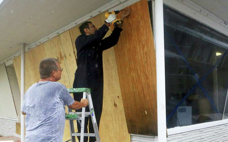 Vimal Patel  boards up windows with the help of Carl Bledsoe, left,  at the Catalina Motel as Hurricane Harvey approaches the Coastal Bend area on Friday, Aug. 25, 2017, in Corpus Christi, Texas. The National Hurricane Center warns that conditions are deteriorating as Hurricane Harvey strengthens and slowly moves toward the Texas coast. Photo: Gabe Hernandez/Corpus Christi Caller-Times Via AP   / Gabe Hernandez/Caller-Times