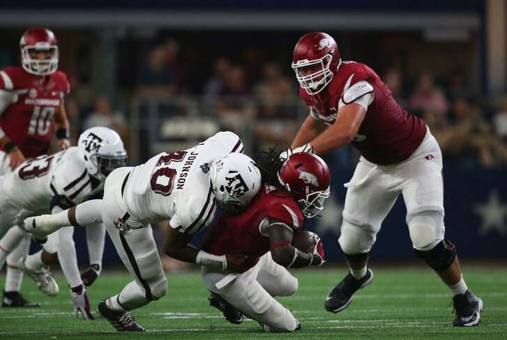 Alex Collins of Arkansas is tackled by Jarrett Johnson of Texas A&M in the Southwest Classic at AT&T Stadium on Sept. 26, 2015 in Arlington, Texas.