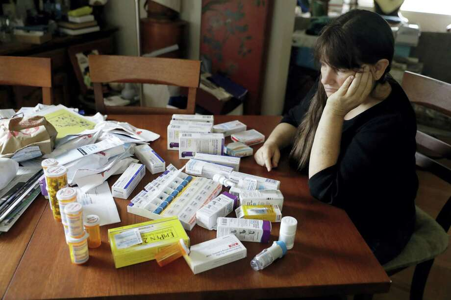 Sara Hayden looks at some of her medications at home on Aug. 10, 2017 in Half Moon Bay, Calif. Hayden lost her job as a data researcher because of medical problems and is now covered by Medi-Cal, as Medicaid is called in California. She has rheumatoid arthritis, and the medication she has to take to keep the disease in check cost thousands of dollars a month. The Medicaid program is a 1960s Great Society creation long criticized by conservatives. But it seems to have emerged even stronger after the Republican failure to pass health overhaul legislation. Photo: AP Photo — Marcio Jose Sanchez  / Copyright 2017 The Associated Press. All rights reserved.
