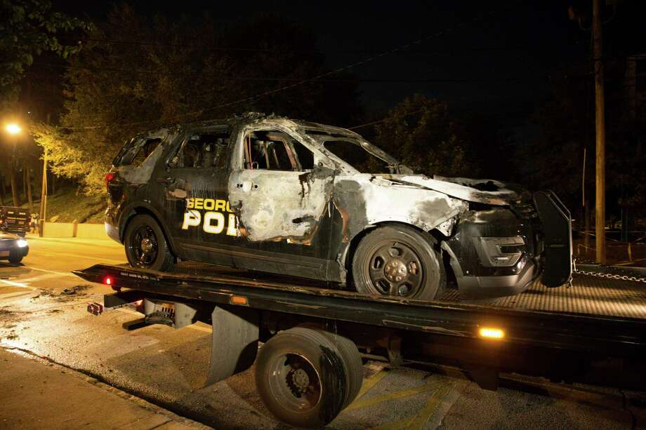 A truck on Monday loads a burned Georgia Tech police vehicle allegedly set ablaze by demonstrators protesting the fatal shooting of Scout Schultz. Photo: Kevin D. Liles, FRE / FR170929 AP