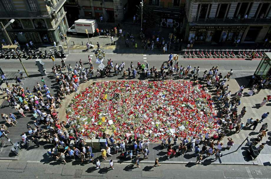 People stand next to candles and flowers placed on the ground, Tuesday, Aug. 22, 2017, after Thursday's terror attack that left many killed and wounded in Barcelona, Spain. The lone fugitive from the Spanish cell that killed several people in and near Barcelona was shot to death Monday after he flashed what turned out to be a fake suicide belt at two troopers who confronted him in a vineyard just outside the city he terrorized, authorities said. Photo: AP Photo/Manu Fernandez   / Copyright 2017 The Associated Press. All rights reserved.