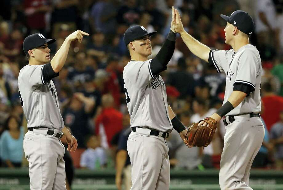 The Yankees' Todd Frazier, right, congratulates Tyler Austin after the Yankees' 4-3 win over the Red Sox at Fenway Park in Boston on Saturday. Photo: Winslow Townson — The Associated Press  / FR170221 AP