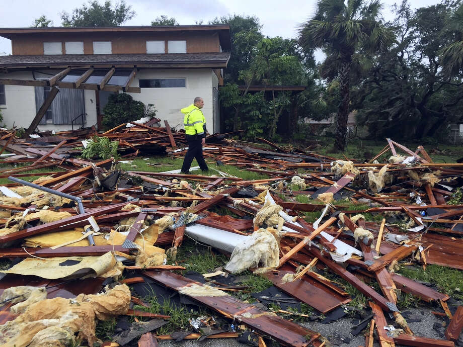 Palm Bay officer Dustin Terkoski walks over debris from a two-story home at Palm Point Subdivision in Brevard County, Fla., after a tornado touched down on Sunday, Sept. 10, 2017. (Red Huber/Orlando Sentinel via AP) Photo: AP / 2017 Orlando Sentinel