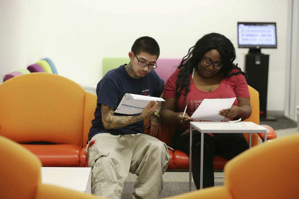 Nick Ainsworth, 23, helps Jarena Mayes, 20, with employment applications at the BiblioTech South facilities on Pleasanton Road, Tuesday, Sept. 19, 2017. The Bexar County's digital library is in its fourth year of existence.