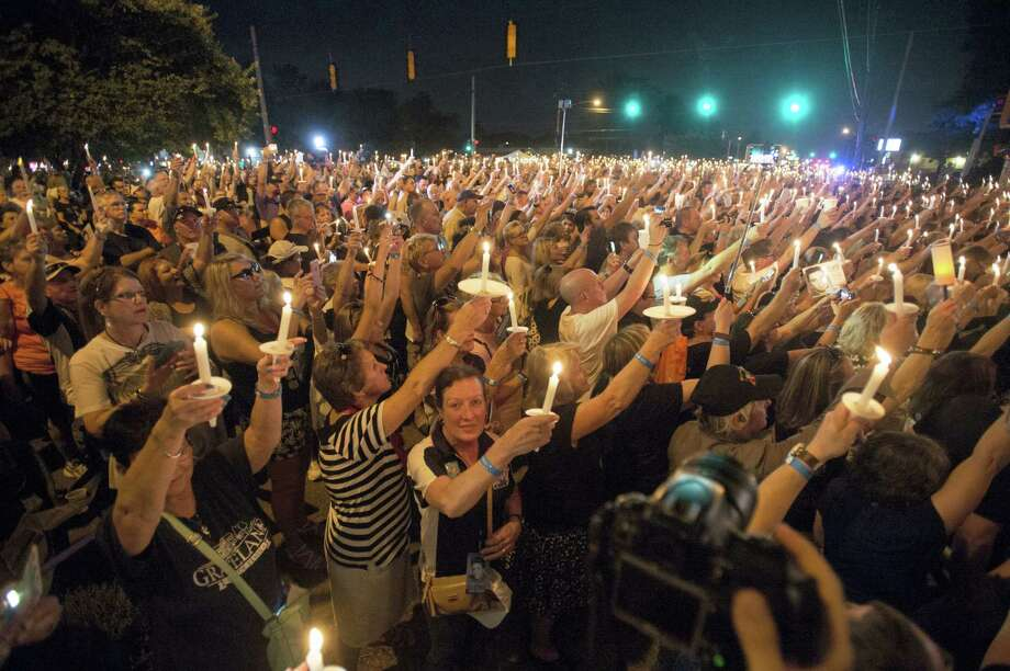 Fans hold candles during a vigil for Elvis Presley at Graceland, Presley's Memphis home, Tuesday, Aug. 15, 2017, in Memphis, Tenn. Fans from around the world are at Graceland for the 40th anniversary of his death. Presley died Aug. 16, 1977. Photo: AP Photo/Brandon Dill   / FR171250 AP