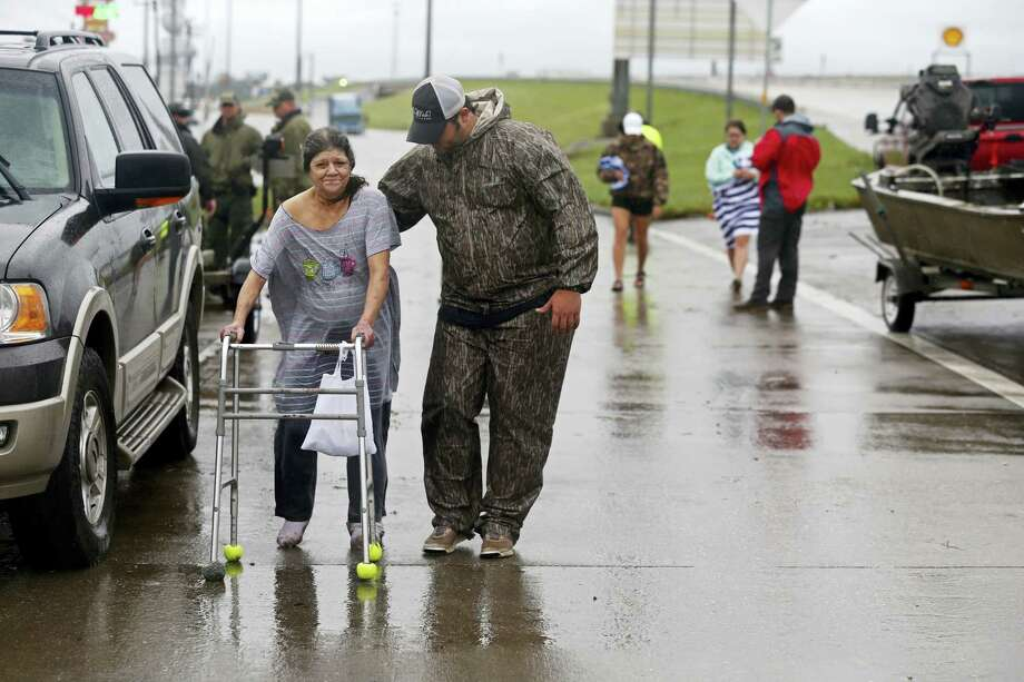 Volunteer Kyle Denison assists Rosemarie Carpenter after she was rescued by boat during flooding from Tropical Storm Harvey in Orange, Texas, Wednesday, Aug. 30, 2017. Photo: AP Photo/Gerald Herbert  / Copyright 2017 The Associated Press. All rights reserved.
