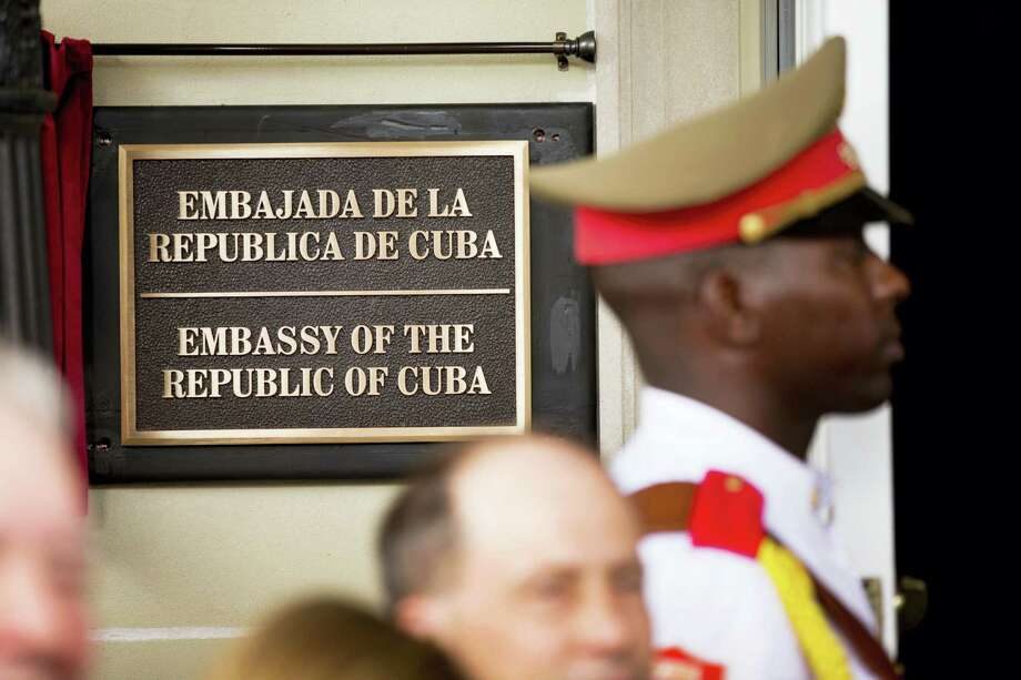 In this July 20, 2015, file photo, a member of the Cuban honor guard stands next to a new plaque at the front door of the newly reopened Cuban embassy in Washington. The State Department has expelled two diplomats from Cuba'Äôs Embassy in Washington following a series of unexplained incidents in Cuba that left U.S. officials there with physical symptoms. Photo: AP Photo/Andrew Harnik, File, Pool   / AP POOL