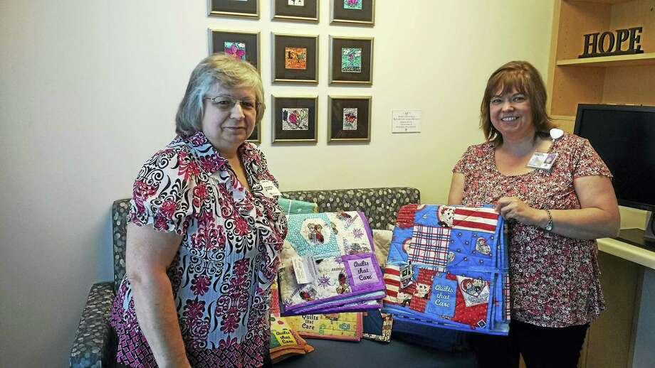 Quilts that Care volunteer Diane Page recently presented a donation to Christine Tatem of Connecticut Children's Medical Center in Hartford. Photo: Contributed Photo
