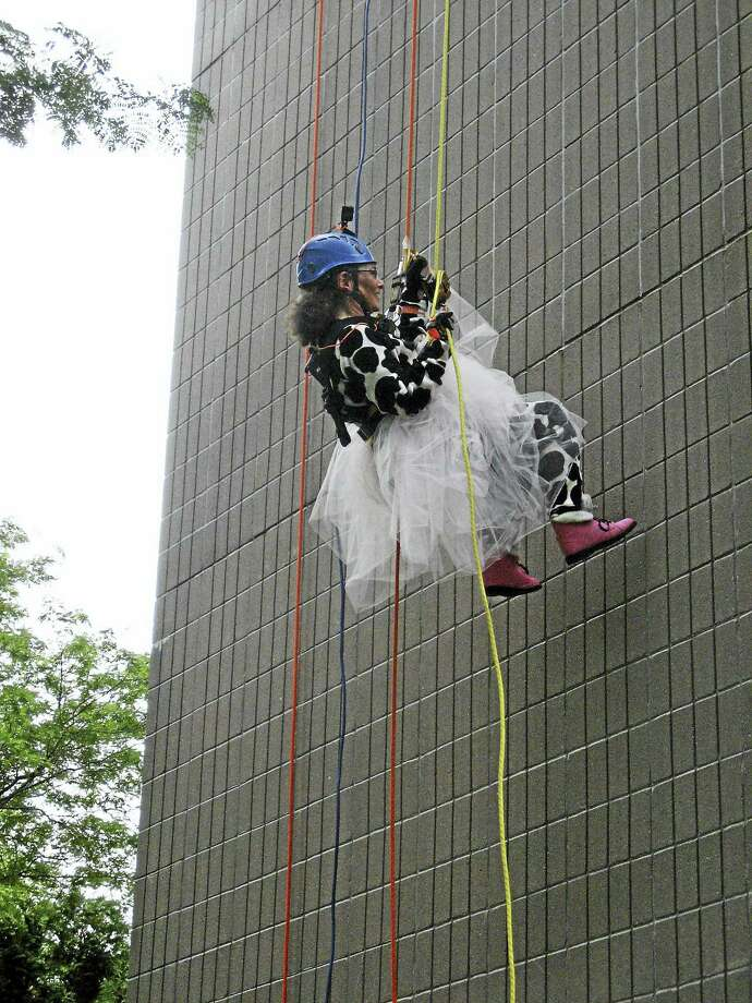 Northwest Connecticut Arts Council director Amy Wynn, dressed in a fluffy tutu and a printed fleece jumpsuit, rappells down the 14-story Torrington Towers building during Saturday's Over the Edge fundraiser. Photo: Emily M. Olson/ Hearst Connecticut Media