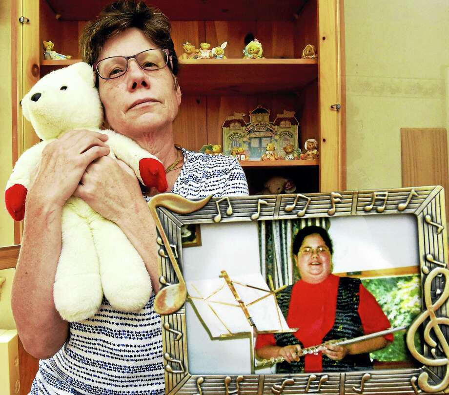 Debbie Morgia of Milford,  whose daughter, Alicia, committed suicide at 18, sits in her daughter's bedroom, now converted into a home office, and holds Alicia's  beloved teddy bear. Photo: Peter Hvizdak /  Hearst Media Connecticut  / New Haven Register
