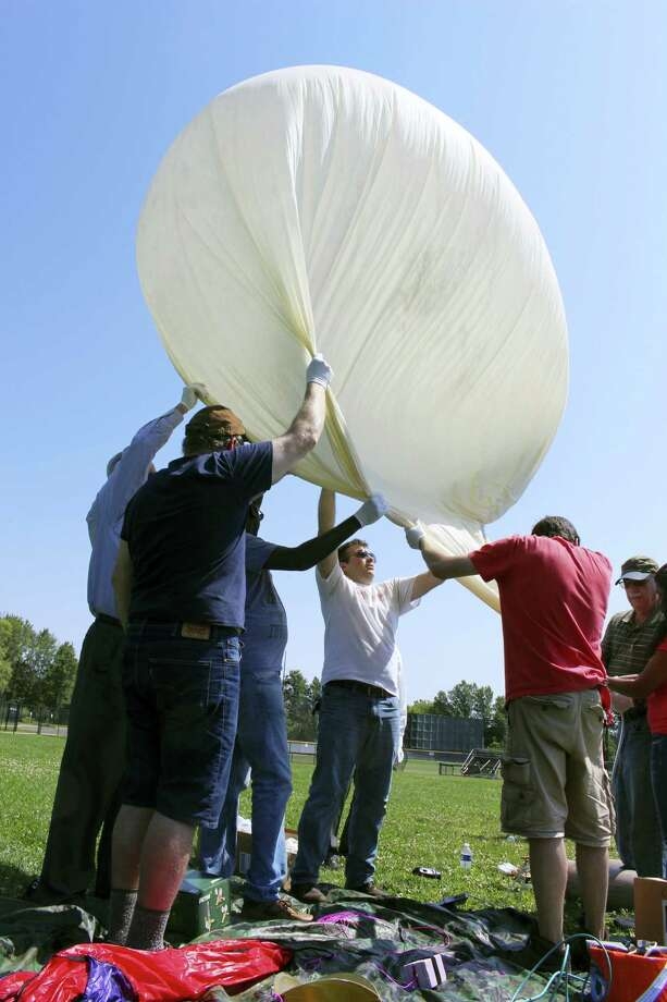 Students and faculty, including Mark Iewicz, center, a mechanical engineering student, prepare to test launch a camera-carrying balloon at the University of Hartford in West Hartford, Conn. on Wednesday, Aug. 9,2017. The team from the University of Bridgeport and the University of Hartford are part a project that will send cameras into the stratosphere to photograph this month's solar eclipse. Photo: Pat Eaton-Robb / AP Photo  / Copyright 2017 The Associated Press. All rights reserved.