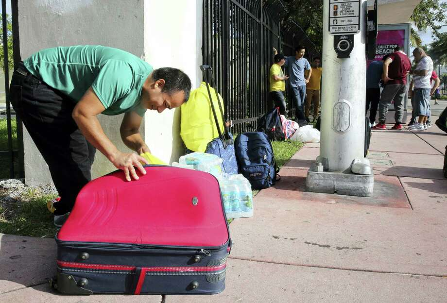 Leonel Geronimo, stuffs food into his suitcase as he and others wait for a bus in anticipation of Hurricane Irma in Miami Beach, Fla., Friday, Sept. 8, 2017. Geronimo wants to get to a shelter off the beach, but is not sure what bus to take or which shelter to go. Photo: AP Photo/Marta Lavandier   / Copyright 2017 The Associated Press. All rights reserved.