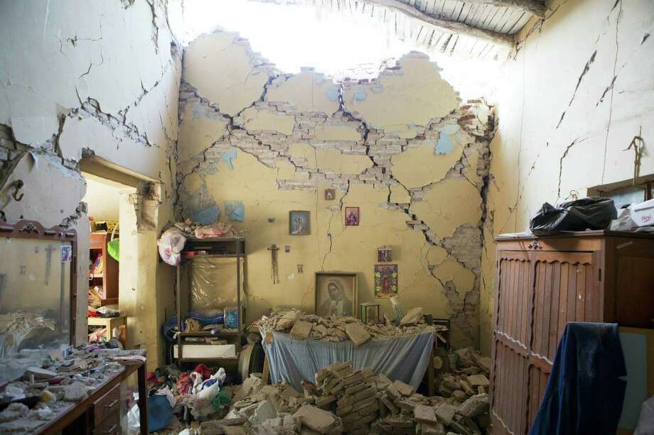 An altar to the Virgin of Guadalupe is covered with fallen debris inside the earth-damaged home where Larissa Garcia, 24, lived with her family in Juchitan, Oaxaca state, Mexico, Saturday, Sept. 9, 2017. The family was caught under rubble when the house partially collapsed, leaving Garcia with a broken arm and her father with a head injury. Her mother, who had to be pulled out from underneath a foot-thick section of wall which collapsed on her back, remains in a wheelchair and unable to walk. Photo: AP Photo/Rebecca Blackwell   / Copyright 2017 The Associated Press. All rights reserved.
