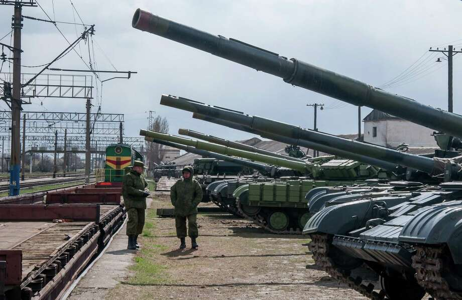 Alexander Polegenko / associated press  Ukrainian armored vehicles are prepared for loading onto a train at a railway station near Simferopol, Crimea. Photo: AP / AP