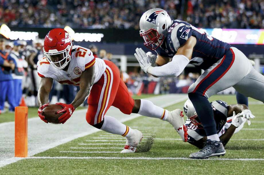 Kansas City Chiefs running back Kareem Hunt (27) crosses the goal line to score a touchdown past Patriots safety Duron Harmon, center, and linebacker Kyle Van Noy, top right, during the second half Thursday in Foxborough, Mass. Photo: Michael Dwyer — The Associated Press  / Copyright 2017 The Associated Press. All rights reserved.