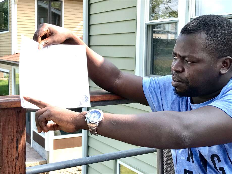 Co-founder Ronnie Sseruyange describes a drawing of a planned new rural orphanage for Jajja's Kids outside Kampala, Uganda. (Paul Grondahl /  Times Union)