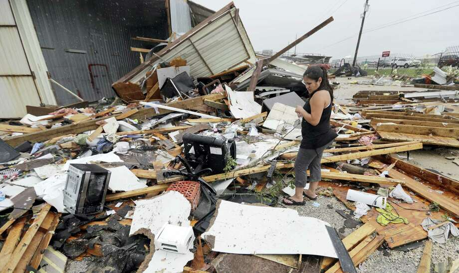 Jennifer Bryant looks over the debris from her family business destroyed by Hurricane Harvey Saturday, Aug. 26, 2017, in Katy, Texas.  Harvey rolled over the Texas Gulf Coast on Saturday, smashing homes and businesses and lashing the shore with wind and rain so intense that drivers were forced off the road because they could not see in front of them. Photo: AP Photo/David J. Phillip   / Copyright 2017 The Associated Press. All rights reserved.