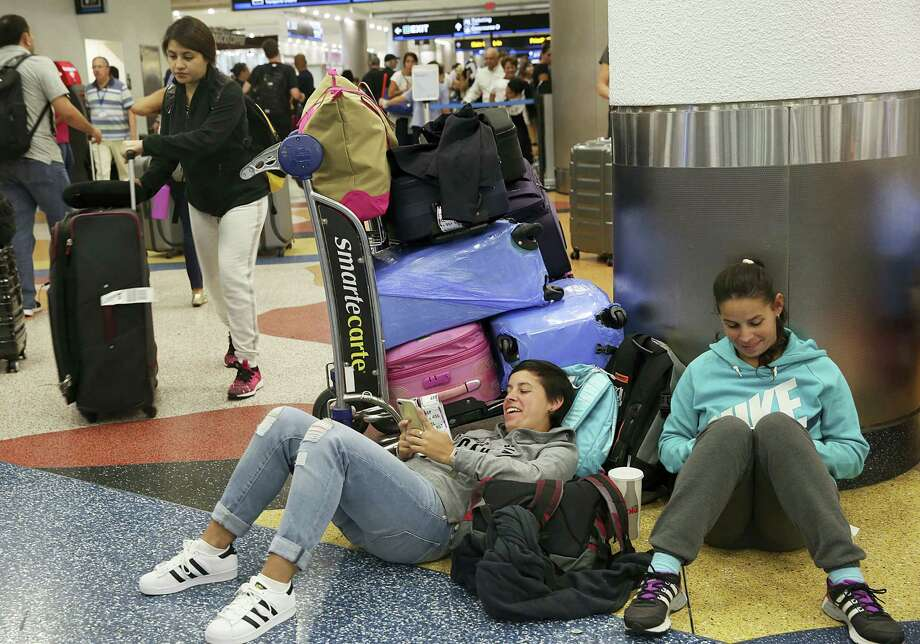 Yanina Fernandez, left, and her sister Liz, wait for an available flight to Argentina after their flight was cancelled at Miami International Airport, Thursday, Sept. 7, 2017, in Miami. South Florida officials are expanding evacuation orders as Hurricane Irma approaches, telling more than a half-million people to seek safety inland. (AP Photo/Marta Lavandier) Photo: AP / Copyright 2017 The Associated Press. All rights reserved.