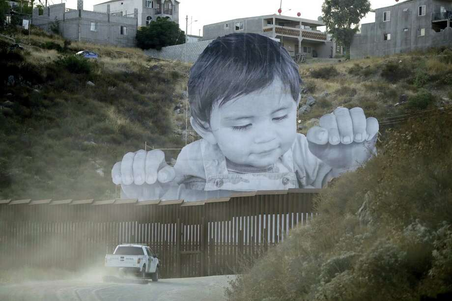 A Border Patrol vehicle drives in front of a mural in Tecate, Mexico, just beyond a border structure Friday, Sept. 8, 2017, in Tecate, Calif. A French artist aiming to prompt discussions about immigration erected a 65-foot-tall cut-out photo of a Mexican boy, pasting it to scaffolding built in Mexico. The image overlooks a section of wall on the California border and will be there for a month. Photo: Gregory Bull / AP Photo  / Copyright 2017 The Associated Press. All rights reserved.