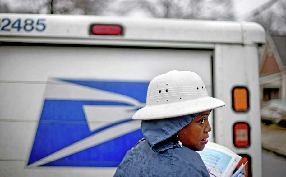 FILE - In this Feb. 7, 2013 file photo, U.S. Postal Service letter carrier Jamesa Euler, delivers mail in the rain in the Cabbagetown neighborhood, in Atlanta. As many high-profile agencies sit idle because of the federal government shutdown, others are humming along just fine. Many of them have escaped the fiscal ax because they pay much of their own way, or enjoy a revenue stream that's insulated from Congress. That means the cable bill and weekly grocery ads will still fill the mailbox, due to the stamps and other items the post office sells. Photo: AP File Photo / AP