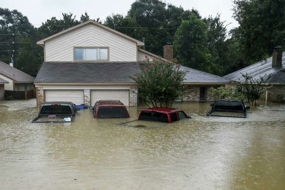 In this file photo, trucks are submerged on Pine Cliff Drive in Houston during heavy rainfall from Tropical Storm Harvey. Few American cities depend on cars as much as Houston, and Harvey's record rainfall left flooded roads and neighborhoods with cars submerged and, in most cases, impossible to salvage. Photo: Michael Ciaglo / Houston Chronicle  / Michael Ciaglo