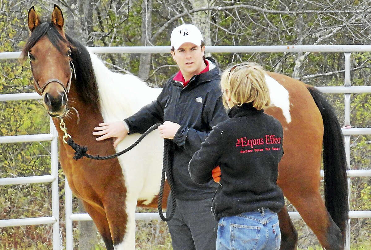 Contributed photoJane Strong, facing away, works with a veteran and Dutch at the Equus Effect in Sharon.