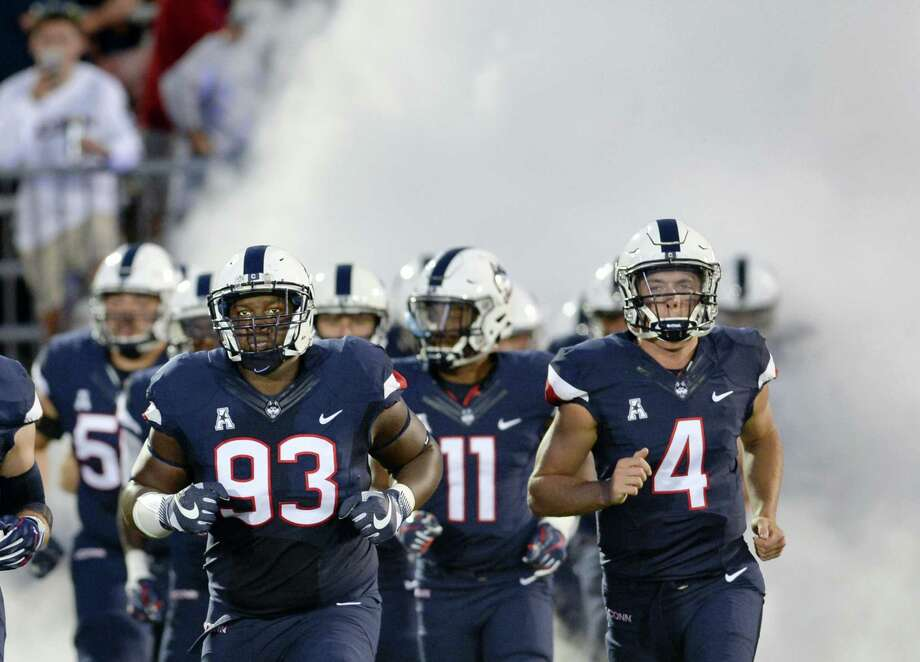 Connecticut defensive lineman Folorunso Fatukasi (93), (11) Connecticut running back Nate Hopkins (11) and Connecticut quarterback Bryant Shirreffs (4) run out of the smoke-filled tunnel before the season opener against Holy Cross Thursday. Hurricane Irma could impact this Saturday's game with South Florida. Photo: Stephen Dunn — The Associated Press  / FR171426 AP