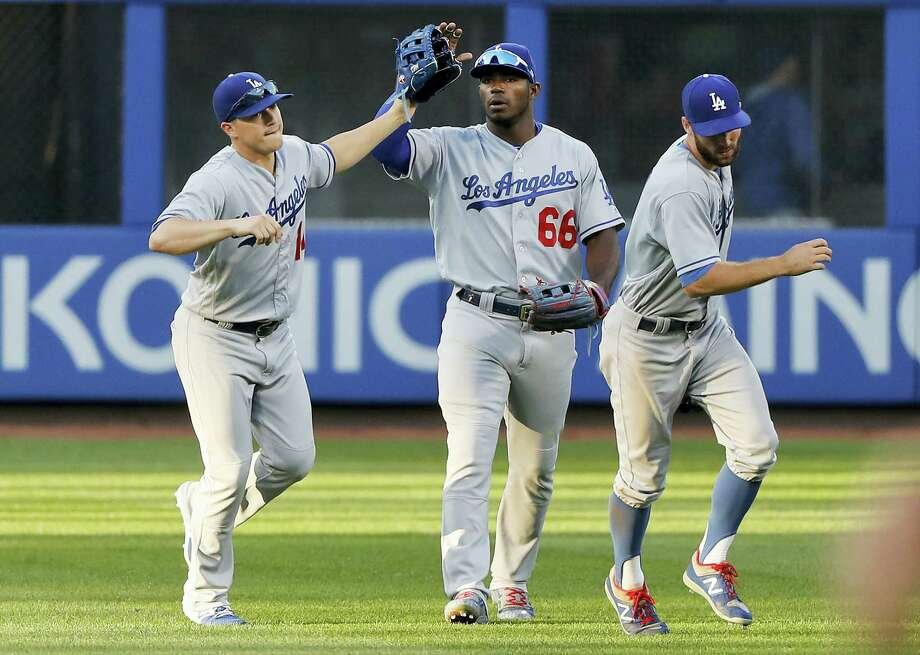 From left, the Dodgers' Enrique Hernandez, Yasiel Puig and Chris Taylor celebrate after beating the Mets on Saturday. Photo: Julie Jacobson — The Associated Press  / Copyright 2017 The Associated Press. All rights reserved.