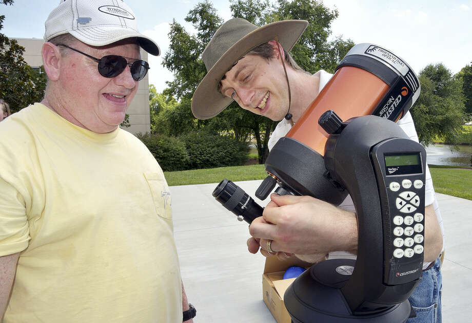 In this June 29, 2017, file photo, David Chrismon, left, a member of Guilford Technical Community College's student astronomy club, the Stellar Society, watches as Steve Desch, an astronomy instructor, sets up a telescope in Jamestown, N.C., that the group will use on their trip to Newberry, S.C. to observe a solar eclipse on Aug. 21. Photo: Laura Greene/The High Point Enterprise Via AP   / The High Point Enterprise