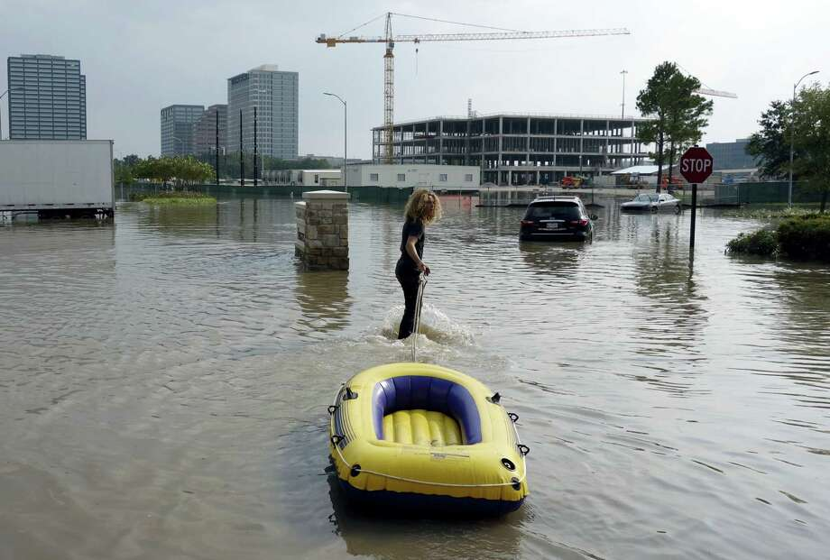 In this Sunday, Sept. 3, 2017 photo, Christian Carr, 17, of Austin, Texas, tows his raft to help residents bring groceries to their flooded Heights Park Row apartment complex in Houston. Equipped with an inflatable yellow raft and fortified with duct tape that might come in handy, Carr and his mother Kelli Shofstall set out on a 165-mile drive from Austin that led them to neighborhood upon neighborhood of dry Houston streets and little sign their help was needed. It would take more than a day of driving around following outdated flood maps before they found a street under water where they could ferry tenants to and from a marooned apartment complex. Photo: Brian Melley / AP Photo  / Copyright 2017 The Associated Press. All rights reserved.
