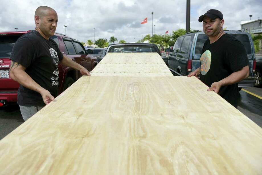 Luis Enrique Garcia, left, and Jose Rivera, load wood panels to be used for boarding up windows in preparation for Hurricane Irma, in Carolina, Puerto Rico, Tuesday, Sept. 5, 2017. Irma grew into a dangerous Category 5 storm, the most powerful seen in the Atlantic in over a decade, and roared toward islands in the northeast Caribbean Tuesday. Photo: Carlos Giusti / AP Photo  / Copyright 2017 The Associated Press. All rights reserved.