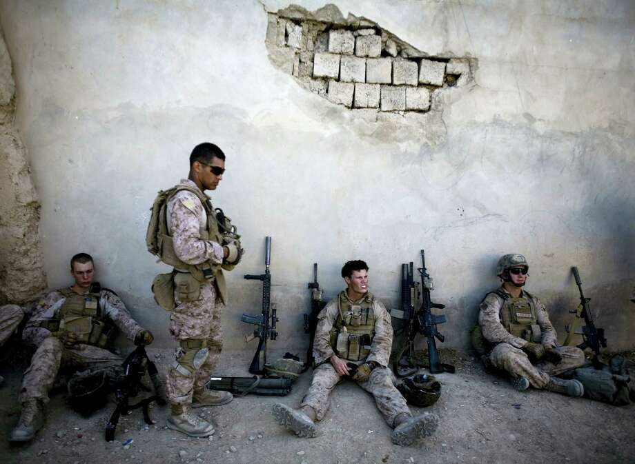 """In this Nov. 3, 2011, file photo, Marines of with India company, 3rd Battalion 5th Marines, First Marine Division, take a break during a patrol in Sangin, south of Kabul, Afghanistan. Reversing his past calls for a speedy exit, President Donald Trump recommitted the United States to the 16-year-old war in Afghanistan, declaring Monday, Aug. 21, 2017, that U.S. troops must """"fight to win."""" He declined to disclose how many more troops will be dispatched to wage America's longest war. Photo: AP Photo/Dusan Vranic   / AP2010"""