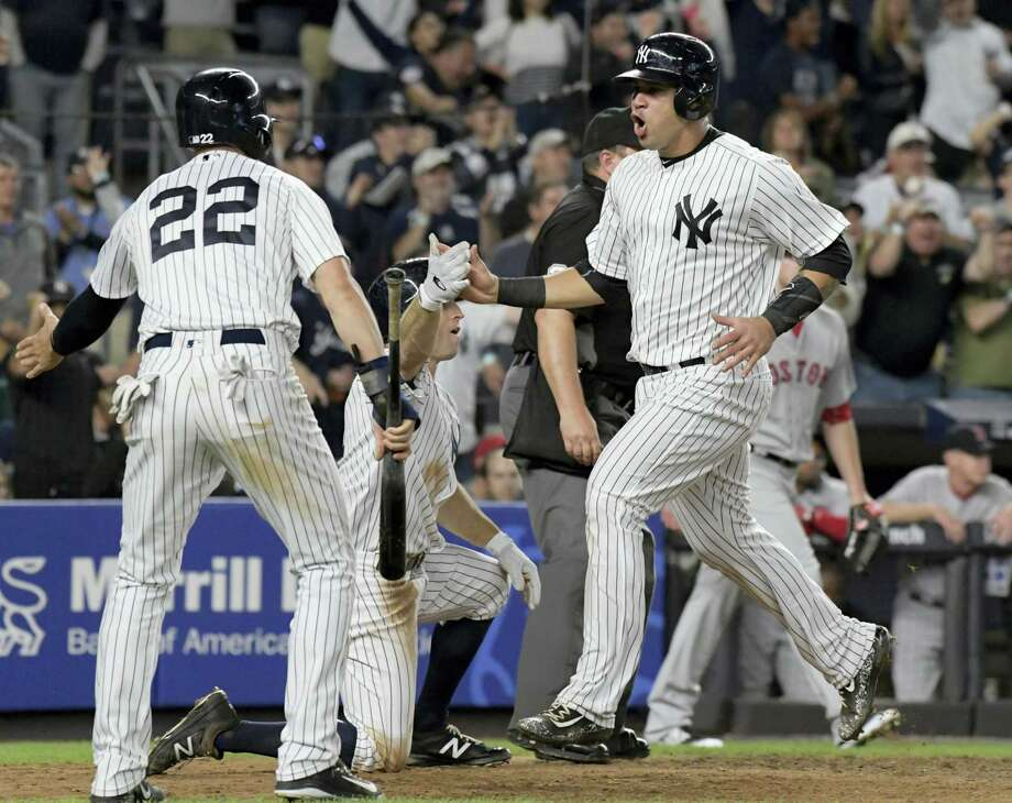 The Yankees' Gary Sanchez, right, celebrates with Jacoby Ellsbury (22) and Brett Gardner after they all scored on a double by Starlin Castro in the sixth inning Sunday. Photo: Bill Kostroun — The Associated Press   / FR51951 AP