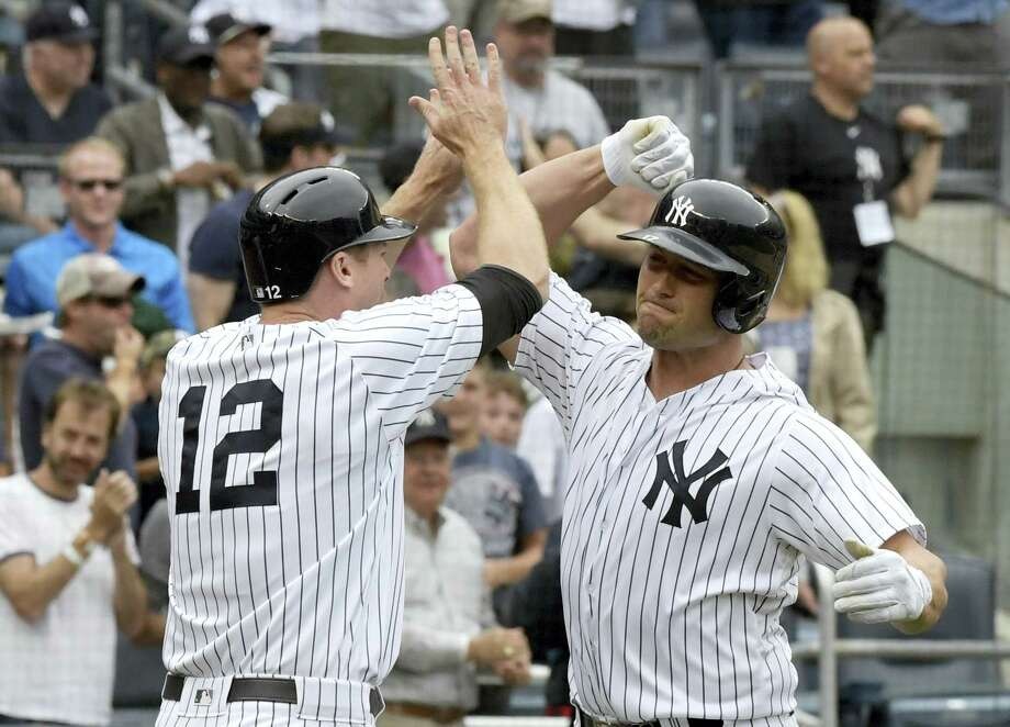 New York Yankees designated hitter Matt Holliday, right, celebrates with Chase Headley (12) after Holliday hit a three-run home run during the sixth inning against the Boston Red Sox Saturday. The Yankees won 5-1. Photo: BILL KOSTROUN - THE ASSOCIATED PRESS  / FR51951 AP