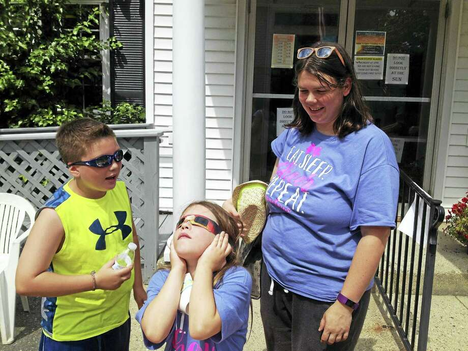 Emily M. Olson / Hearst Connecticut Media From left, Zach Krystopa, 9, Sarah Krystopa, 7, and their mother Katelyn Krystopa take turns observing the sun at Blondin Shea Eye Care on Monday during the practice's solar eclipse party. the Krystopas are residents of New Milford; Katelyn has been a patient since her early teens. Photo: Digital First Media