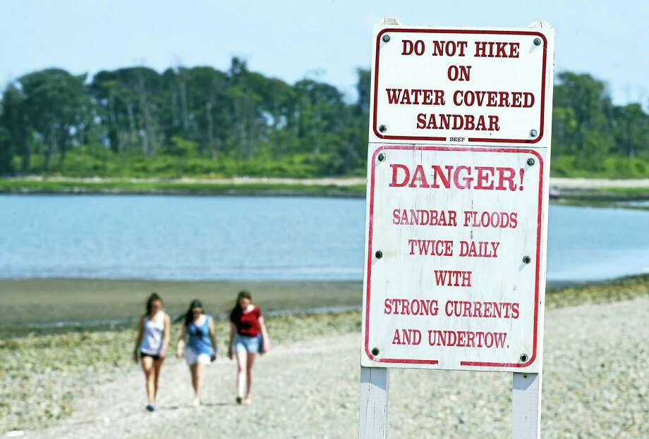 Signs posted at Silver Sands State Park in Milford warn of the danger of crossing the sandbar to Charles Island when it is covered with water. Photo: File Photo