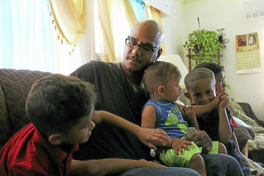 Wigberto 'George' Ortiz sits on a couch with his sons, from left: Lorenzo, 6; Matteo, 16 months; Marcelo, 4; and Vitally, 7, in New Britain. Ortiz completed a program aimed at helping fathers who have been charged in domestic violence incidents. Photo: Esteban L. Hernandez / Hearst Connecticut Media