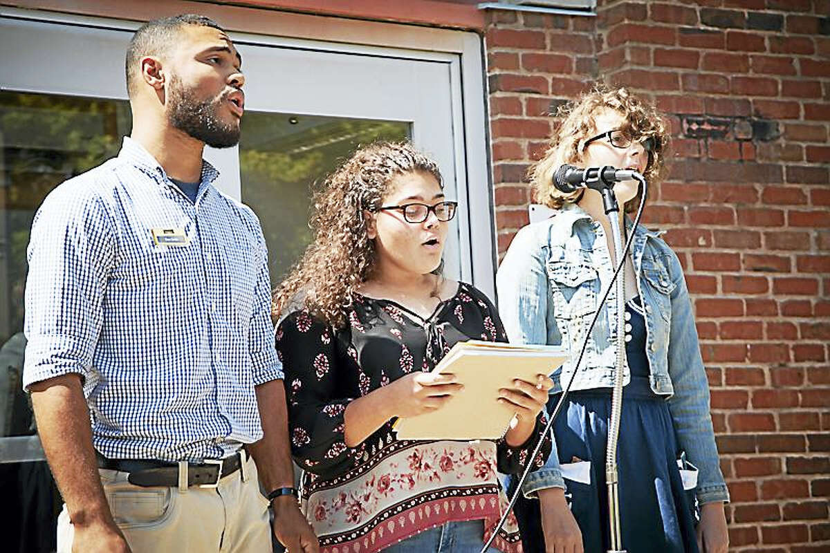 """Middlesex Community College students Daniel Ortiz, Gilianne Oyolo and Marina Capezzone sang """"This Land is Your Land"""" at the school's recent CommUNITY event."""