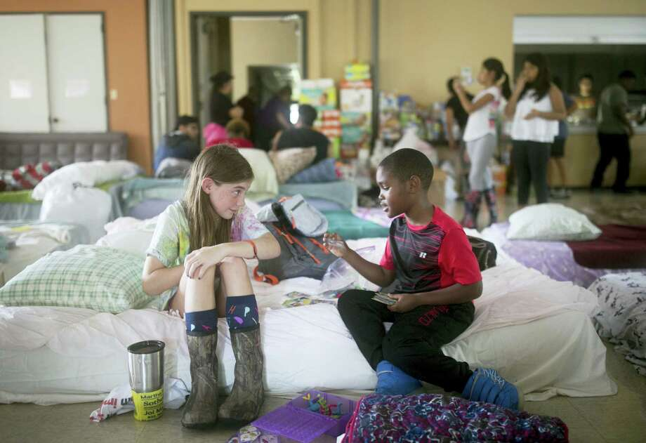 Volunteer Elizabeth Hill, 8, plays with evacuee Skyler Smith, 7, at a shelter at St. Thomas Presbyterian Church in west Houston after Hurricane Harvey Aug. 29. Photo: Jay Janner — Austin American-Statesman Via AP  / Austin American-Statesman