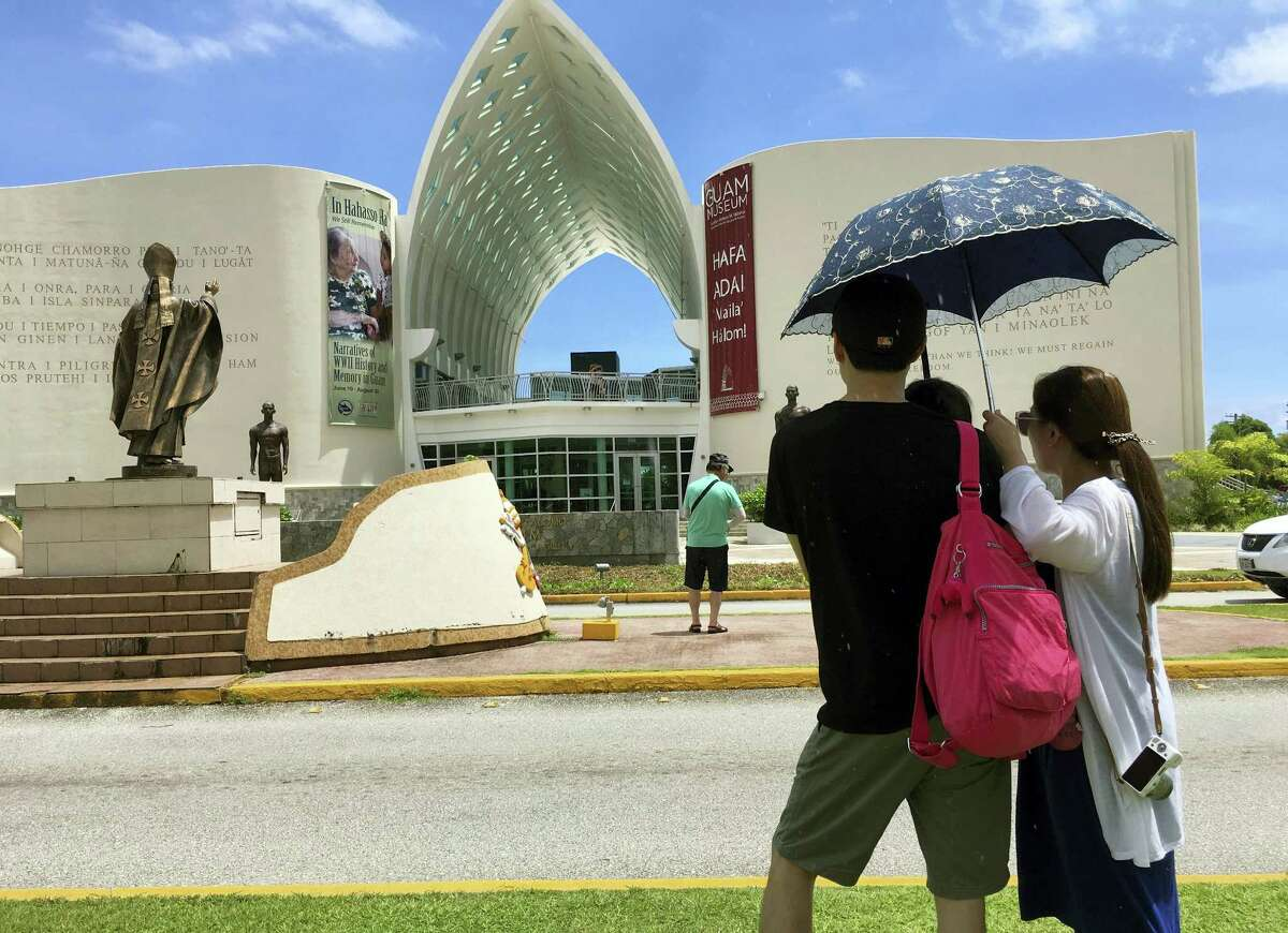 Tourists walk outside of Dulce Nombre de Maria Cathedral Basilica in Hagatna, Guam on Friday, Aug. 11, 2017. The small U.S. territory of Guam has become a focal point after North Korea's army threatened to use ballistic missiles to attack the island.