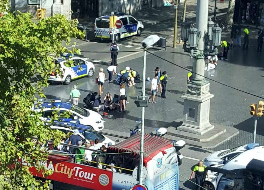 Injured are helped by responders as a tour bus passes by after a white van jumped the sidewalk in the historic Las Ramblas district of Barcelona, Spain, crashing into a summer crowd of residents and tourists Thursday, Aug. 17, 2017.   According to witnesses the white van swerved from side to side as it drove into tourists and residents. Photo: Daniel Vil Via AP   / Copyright 2017 The Associated Press. All rights reserved.
