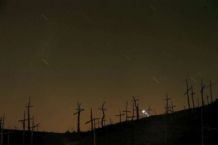 This Friday, Aug. 12, 2016, file photo made with a long exposure shows streaks in the sky during a Perseid meteor shower, seen behind crosses in Marganell, Spain. NASA's meteor expert, Bill Cooke, says astronomers are projecting a slightly higher than normal rate of 150 meteors per hour across North America. But the bright moon will wash out the finer Perseids. So, the viewing rate will be more like 30 to 40 meteors an hour. Peak viewing will be Friday night, Aug. 11, 2017, early Saturday, Saturday night and early Sunday. Photo: AP Photo/Manu Fernandez   / Copyright 2016 The Associated Press. All rights reserved. This material may not be published, broadcast, rewritten or redistribu