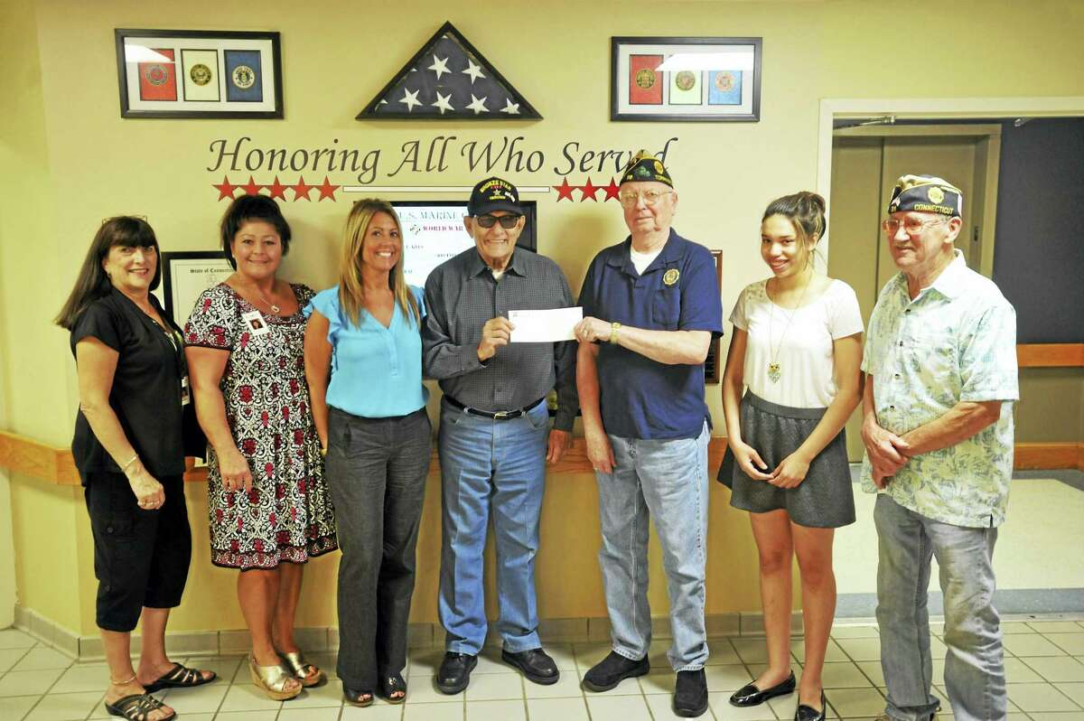 Veteran Mike Galitello, who served in the U.S. Army as a corporal during the Korean War, donated proceeds from his novels to the Torrington Veterans Service Office Thursday at Litchfield Woods Health Care Center. From left are Sally Goddard, admissions; Sue Tonetti, human resources; Administrator Denise Quarles; Galitello, office director Bud Atwood; ghostwriter and Northwestern Connecticut Community College student Olivia Pinto; and American Legion Post 38 Commander Bruce Pinto.