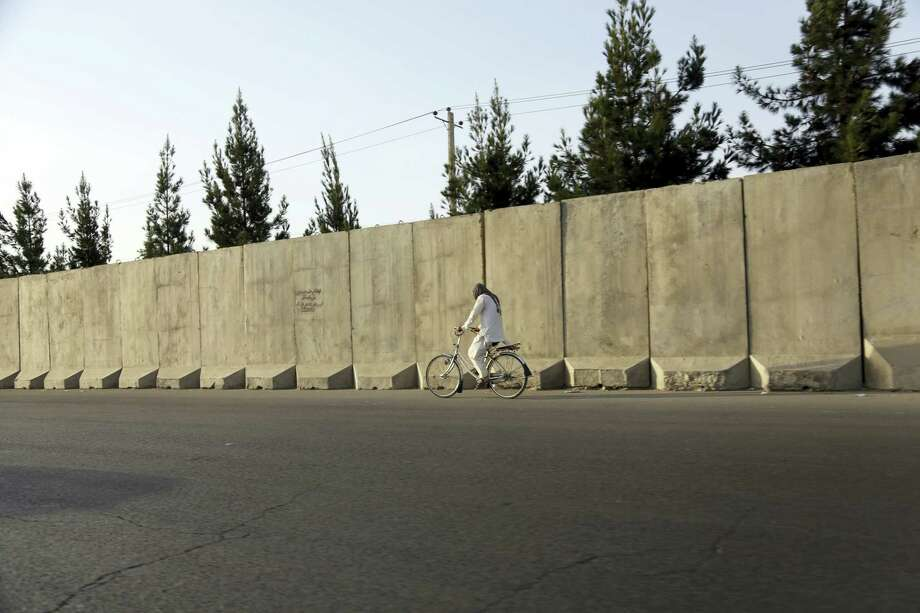 In this Monday, July 31, 2017, photo, an Afghan man rides his bicycle walks past blast walls in Kabul, Afghanistan. A U.S. watchdog says unprecedented security restrictions are making it difficult to monitor Afghanistan projects that are costing hundreds of millions of U.S. tax dollars. Despite tight security, an explosion inside a minority Shiite mosque in western Herat, on the border with Iran, has killed at least 20 people. Photo: AP Photos/Rahmat Gul   / Copyright 2017 The Associated Press. All rights reserved.