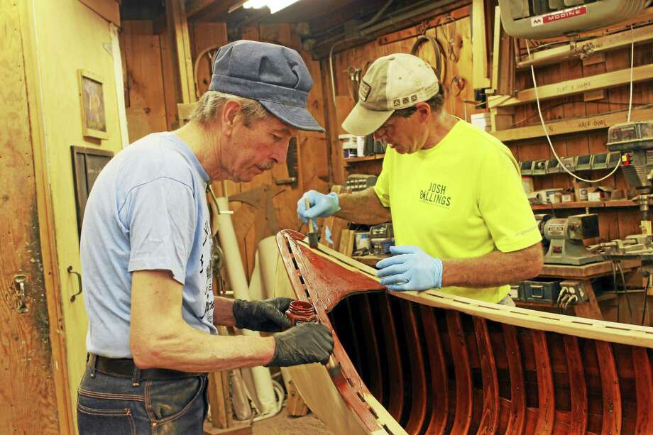 Craftsmen Greg Millard, left, and Kerry Jassen, both trustees of the Colebrook Land Conservancy, work with care restoring the classic Indian model canoe to its original beauty. The canoe is being raffled by the conservancy as a fund raiser. The winning ticket will be drawn Sept. 9. Photo: Contributed Photos