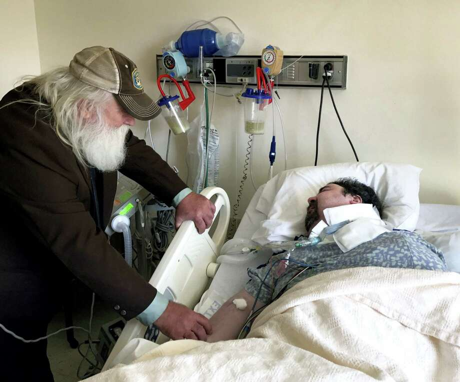 In this April 18, 2017 photo, Walter Wenger visits his severely disabled son, Steven, in a hospital in Kingston, N.Y, where he was moved after maggots were twice found in the area around his breathing tube while living in a state group home. The Associated Press obtained a confidential report on the state investigation that determined the 2016 infestations at the group home in Rome, N.Y., were the result of neglect by caregivers. In most states, details of abuse and neglect investigations in state-regulated institutions for the disabled are almost never made public. Photo: AP Photo — David Klepper  / Copyright 2017 The Associated Press. All rights reserved.