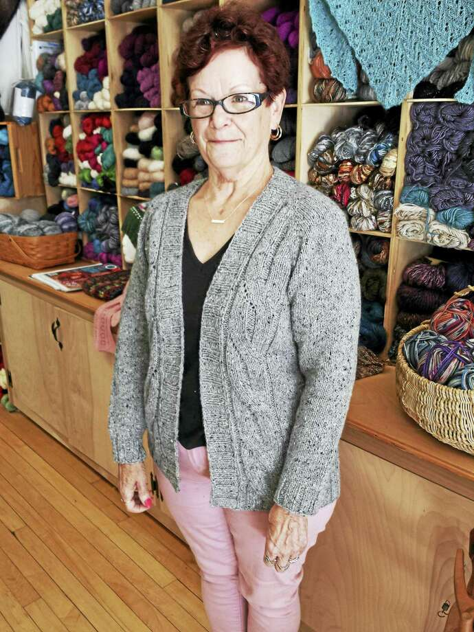 Sandy, a friend of In Sheep's Clothing, models her own cardigan sweater. The shop offers knitting classes every Thursday night. Photo: Photo By Ginger Balch