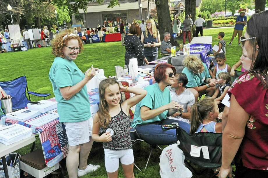"""The Torrington schools held a """"meet-and-greet"""" ahead of the coming school year Thursday in Coe Memorial Park. Above, families and teachers enjoy the summer weather near a collection of tables providing information on each of the city's schools. Photo: Ben Lambert / Hearst Connecticut Media"""
